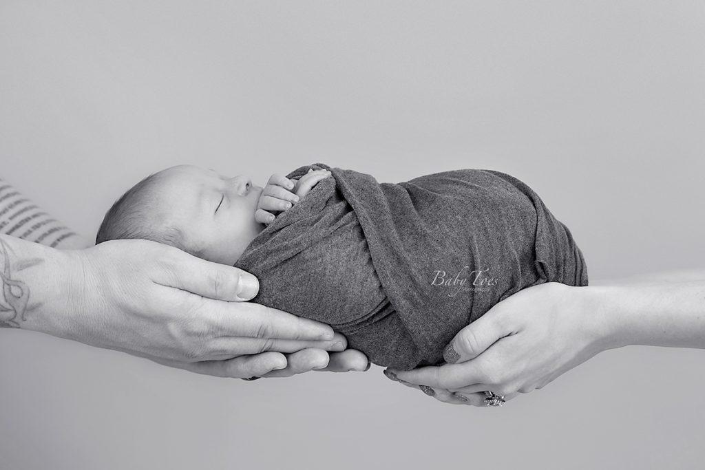 newborn in parent's hands