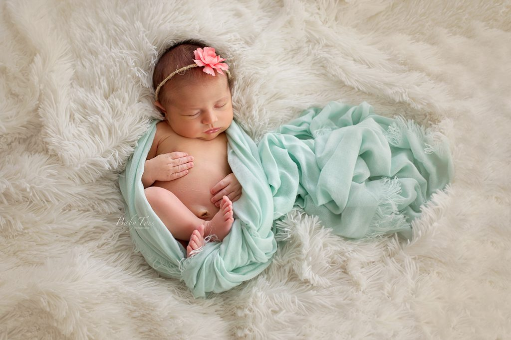 newborn girl in mint wrap